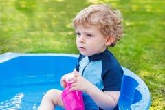 Entzückender blonder Kleinkindjunge, der mit Wasser, draußen spielt Stockbilder