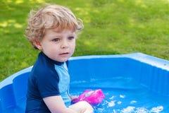 Entzückender blonder Kleinkindjunge, der mit Wasser, draußen spielt Stockfoto