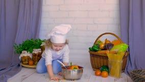 Entzückender Chef des kleinen Mädchens, der gesundes Lebensmittel unter Verwendung des Gemüses und der Wanne kocht stock footage
