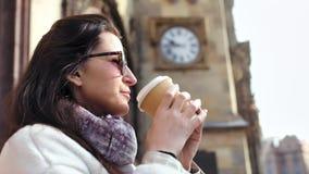 Entzückender Entspannungstrinkender Kaffee der jungen Frau der Nahaufnahme umgeben durch schöne mittelalterliche Architektur stock video