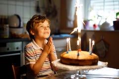 Entzückender glücklicher blonder Kleinkindjunge, der seinen Geburtstag feiert Stockfotografie