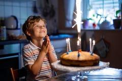 Entzückender glücklicher blonder Kleinkindjunge, der seinen Geburtstag feiert Stockfoto