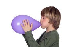Entzückender jugendlicher Junge, der einen purpurroten Ballon explodiert Stockbild