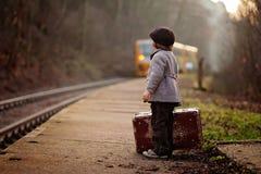 Entzückender Junge auf einem Bahnhof, auf den Zug mit Koffer und Teddybären wartend lizenzfreie stockbilder