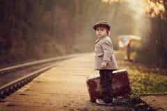Entzückender Junge auf einem Bahnhof, auf den Zug mit Koffer und Teddybären wartend lizenzfreies stockbild