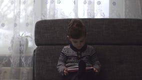 Entzückender Junge, der auf dem Sofa im Wohnzimmer sitzt und mit Gerät spielt Kind, das wie man Smartphone lernt, benutzt