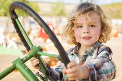 Entzückender Junge, der draußen auf einem alten Traktor spielt Lizenzfreie Stockbilder