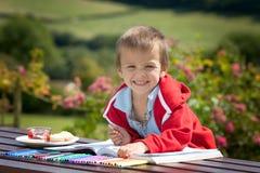Entzückender Junge in der roten Strickjacke, eine Malerei in einem Buch zeichnend, übertreffen Stockfoto