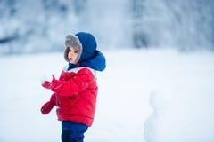 Entzückender Junge, der Spaß mit Schnee hat Stockfoto