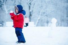 Entzückender Junge, der Spaß mit Schnee hat Stockfotografie