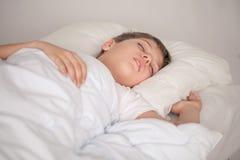 Entzückender Junge, der in weiße Pyjamas schläft Stockfotografie