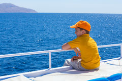 Entzückender Junge, der zum blauen Meer vom Yachtbrett schaut Stockfoto