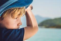 Entzückender Junge, der zum blauen Meer vom Yachtbrett am sonnigen Tag schaut Lizenzfreies Stockfoto