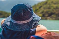 Entzückender Junge, der zum blauen Meer vom Yachtbrett am sonnigen Tag schaut Stockfoto