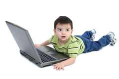 Entzückender Junge mit dem Legen auf den weißen Fußboden, der an Laptop arbeitet Stockfotografie