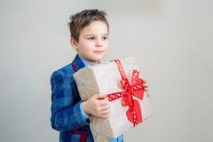 Entzückender Junge mit einer Geschenkbox auf einem hellen Hintergrund stockfoto