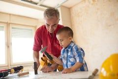 Entzückender Junge und ältere der Mann, die Hammer hält und klopfen einen Nagel stockbild