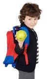 Entzückender Jungenkursteilnehmer mit Rucksack und Apfel Lizenzfreies Stockbild