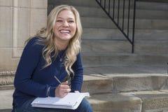 Entzückender junger blonder Student auf dem Campus Stockfotos