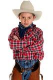 Entzückender junger Cowboy, der die Kameraarme gefaltet betrachtet lizenzfreie stockbilder