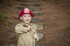 Entzückender Kinderjunge mit dem Feuerwehrmann-Hut, der draußen spielt Stockfotos