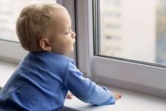 Entzückender kleiner blonder Kinderjunge, der nahe Fenster sitzt und draußen schaut Lizenzfreie Stockfotografie