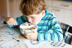 Entzückender kleiner blonder Schulkinderjunge, der Getreide mit Milch und Beeren für Frühstück oder das Mittagessen isst Stockfotografie