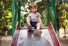 Entzückender kleiner Junge, der auf einem Dia spielt Stockfotografie