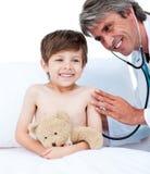 Entzückender kleiner Junge, der eine medizinische Überprüfung bedient Lizenzfreie Stockfotos