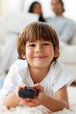 Entzückender kleiner Junge, der Fernsieht, auf dem Fußboden zu liegen Lizenzfreies Stockfoto