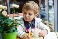 Entzückender kleiner Junge, der Frozen-Jogurt-Eiscreme im Café isst Stockfoto