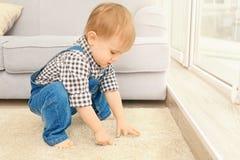 Entzückender kleiner Junge, der im Raum spielt Stockbild