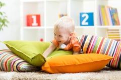 Entzückender kleiner Junge, der mit Kissen auf Boden im Kinderraum spielt lizenzfreies stockbild