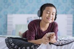 Entzückender kleiner Junge, der Musik im Schlafzimmer genießt Stockfotografie
