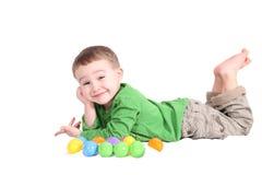 Entzückender kleiner Junge, der sich mit buntem Osten hinlegt Stockbild