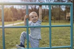 Entzückender kleiner Junge, der Spaß auf Spielplatz hat lizenzfreies stockbild