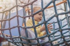 Entzückender kleiner Junge mit den blauen Augen, die Spaß auf Spielplatz haben lizenzfreies stockfoto