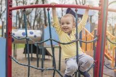 Entzückender kleiner Junge mit den blauen Augen, die den Spaß im Freien haben stockbild