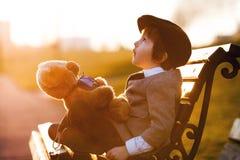 Entzückender kleiner Junge mit seinem Teddybärfreund im Park Lizenzfreies Stockbild