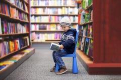 Entzückender kleiner Junge, sitzend in einem Buchladen Lizenzfreie Stockbilder