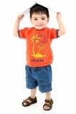 Entzückender Kleinkind-Junge mit Buch auf Kopf Lizenzfreies Stockfoto