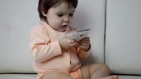 Entzückender Kleinkindjunge, der auf dem Sofa im Wohnzimmer sitzt und mit Smartphone spielt Kind, das wie man lernt, verwendet stock footage