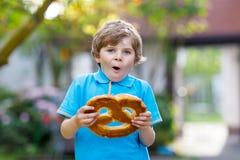 Entzückender Kleinkindjunge, der enorme große bayerische deutsche Brezel isst Lizenzfreies Stockfoto