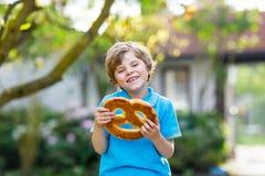 Entzückender Kleinkindjunge, der enorme große bayerische deutsche Brezel isst Stockfoto