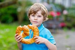 Entzückender Kleinkindjunge, der enorme große bayerische deutsche Brezel isst Stockfotos