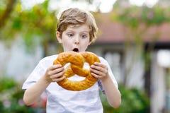 Entzückender Kleinkindjunge, der enorme große bayerische deutsche Brezel isst Lizenzfreie Stockbilder