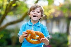 Entzückender Kleinkindjunge, der enorme große bayerische deutsche Brezel isst Stockbild