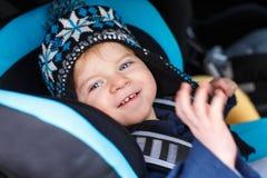 Entzückender Kleinkindjunge, der im Sicherheitsautositz sitzt Stockbilder