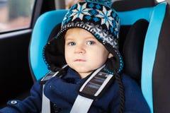 Entzückender Kleinkindjunge, der im Sicherheitsautositz sitzt Lizenzfreie Stockbilder