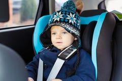 Entzückender Kleinkindjunge, der im Sicherheitsautositz sitzt Lizenzfreies Stockbild